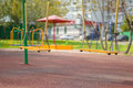 Empty Chain Swings On Summer Playground Royalty Free Stock Images - 27064919