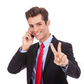 Business Man Making Victory Sign On  Phone Stock Images - 27075634