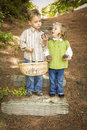 Two Children With Basket Collecting Pine Cones Stock Photos - 27115163