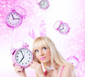 Beautiful Girl In Bunny Ears Holding Clock Royalty Free Stock Image - 27227366