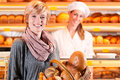 Salesperson With Female Customer In Bakery Royalty Free Stock Photography - 27368827