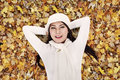 Asian Woman Laying Happily On Autumn Leaves Stock Images - 27555604