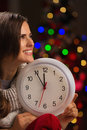 Woman Showing Clock In Front Of Christmas Lights Stock Image - 27560381