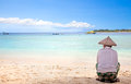 Indonesian Man With Straw Hat Sitting On The Beach Royalty Free Stock Images - 28028139