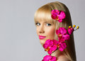 Beautiful Blonde Young Girl With Orchid Flowers On Grey Backgrou Royalty Free Stock Photos - 28256418