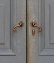 Old-Fashioned Bronze Handles Of Gray Door Royalty Free Stock Photos - 28291458