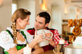 Young Couple In Traditional Bavarian Tracht In Restaurant Or Pub Royalty Free Stock Image - 28438726