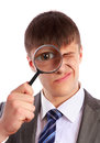 Young Businessman Looks Through A Magnifying Glass Royalty Free Stock Image - 28537136