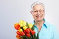 Old Lady With Flowers Smiling Stock Photos - 28598943