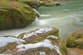 Snow On Mossy Rocks Beside Smooth Cool Flowing River Water Royalty Free Stock Photos - 28724578