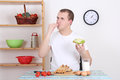 Young Man Eating Tasty Sandwich In The Kitchen Stock Photo - 28802060