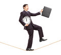 Businessman Holding Clock And Briefcase And Walking On A Rope Royalty Free Stock Photography - 28813157