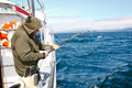Alaska - Senior Man Fishing Reeling In Halibut Royalty Free Stock Photos - 28868458