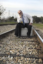 Worried Senior Businessman Sits On Suitcase On Railroad Track Royalty Free Stock Photo - 28903545