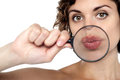 Lady Holding Magnifying Glass In Front Of Her Lips Royalty Free Stock Photos - 29071078
