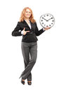 Blond Mature Woman Standing And Pointing On A Wall Clock Stock Photos - 29114763