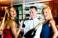 Happy Friends With A Bottle Champagne At Bar Royalty Free Stock Image - 29524906