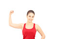 Young Smiling Woman Showing Her Bicep Muscle Royalty Free Stock Photo - 29559815