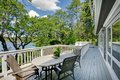 Large Long Balcony Home Exterior With Table And Chairs, Lake View. Royalty Free Stock Photo - 29562755