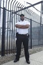 Security Guard Standing In Front Of Prison Fence Stock Photography - 29666402