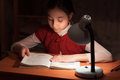 Girl At Desk Reading A Book By Light Of The Lamp Royalty Free Stock Photography - 29796117