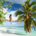 Woman Siting Upon Palm Tree On The Beach Stock Photos - 29874483