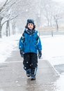 Hispanic Child Walking In The Sidewalk On A Snowy Day Royalty Free Stock Photography - 30374597
