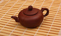 Brown Teapot On The Bamboo Table-cloth Royalty Free Stock Images - 30557119