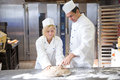 Baker Instruction Apprentice In Kneading Bread Dough Royalty Free Stock Photography - 30566107