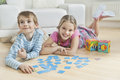 Portrait Of A Girl And Little Brother Lying On Floor With Cards Stock Image - 30853341