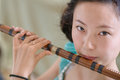 Chinese Girl Blowing Bamboo Flute Stock Photography - 30884232