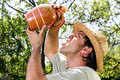 Thirsty Young Man With Straw Hat Drinking Water From A Ceramic J Royalty Free Stock Photography - 30923427