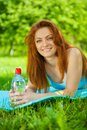 Beautyful Redhead Girl On Grass With Bottle Of Water Stock Image - 31284041