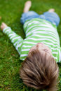 Young Child Relaxing On Green Grass Royalty Free Stock Photography - 31341907