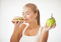 Woman Smelling Hamburger And Holding Apple Royalty Free Stock Photo - 31423395