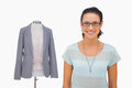Designer Smiling At Camera With Mannequin Behind Royalty Free Stock Images - 31546669