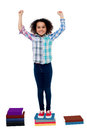 Excited Pretty School Child Standing On Books Stock Photos - 31602933