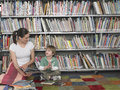 Woman Reading Book To Boy In Library Stock Photos - 31828853