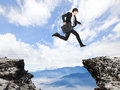 Businessman Jumping Over Danger Precipice Royalty Free Stock Images - 31847189
