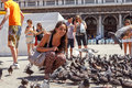 ITALY, VENICE - JULY 2012: Woman With Pigeons On Most Famous Square July 16, 2012 In Venice. More Than 20 Million Tourists Come To Royalty Free Stock Photos - 31889228
