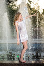 Attractive Girl In White Short Dress Sitting On Parapet Near The Fountain In The Summer Hottest Day Royalty Free Stock Image - 31938576