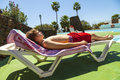 Handsome Teenage Boy Rests On A Beach Couch At The Pool Stock Photos - 31962403