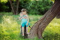 Two Sisters Sitting On A Tree Stump In A Beautiful Park In The Summer Stock Image - 31969941