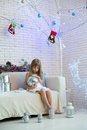 Little Girl Sitting On The Sofa With Christmas Gifts And Playing Stock Photo - 32483480