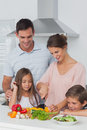 Woman Cutting Vegetables Next To Her Children Stock Photos - 32510753