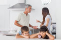 Unhappy Siblings Sitting In Kitchen With Their Parents Who Are F Royalty Free Stock Photography - 32516237