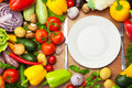 Fresh Organic Vegetables Around White Plate With Knife And Fork Royalty Free Stock Image - 32587846