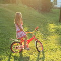 Girl Sitting On A Bike In Sun Royalty Free Stock Photography - 32679477