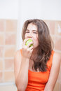 Teenage Girl In Orange T-shirt Eating A Green Apple Royalty Free Stock Photos - 32682258
