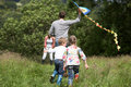 Rear View Of Family Flying Kite In Countryside Stock Photos - 33075923